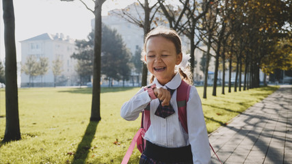 Child girl in school uniform is walking quickly in the park and talking on her pink wrist smart watches and laughing at sunny autumn weather, trees along the way.