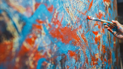 Fototapete - Close-up Shot of Female Artist Hand, Holding Paint Brush and Drawing Painting with Red Paint. Colorful, Emotional Oil Painting. Contemporary Painter Creating Modern Abstract Piece of Fine Art