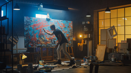Fototapete - Talented Male Artist Energetically and Violently Using Paint Brush he Creates Modern Masterpiece of the Oil Painting. Dark and Messy Creative Studio with Large Canvas of Striking Colors