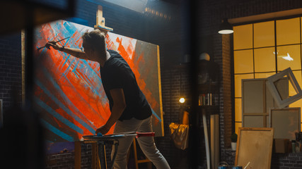 Fototapete - Talented male Artist Works on Abstract Oil Painting, with Broad Strokes of Paint Brush he Creates Modern Masterpiece. Dark and Messy Creative Studio where Large Canvas Stands on Easel Illuminated