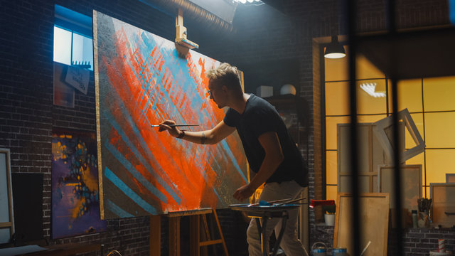Talented Male Artist Energetically and Violently Draws with Paint Brush, He Creates Modern Masterpiece of the Oil Painting. Creative Studio with Large Canvas of Striking Colors. Back View Shot