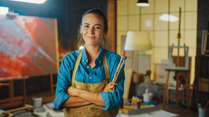Fototapete - Professional Young Female Artist Dirty with Paint, Wearing Apron, Arms Crossed while Holding Brushes, Looks at the Camera with a Smile. Authentic Creative Studio with Large Canvas. Face Portrait