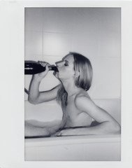 Young Androgyne Man in bath with bottle of red wine