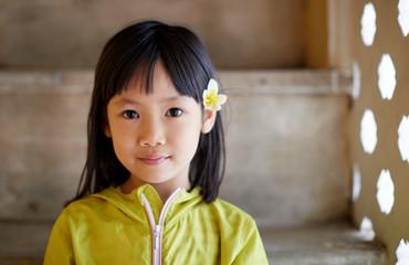 Cute Asian little girl wearing plumeria flowers in front of quaint windows. Travel in Hanoi