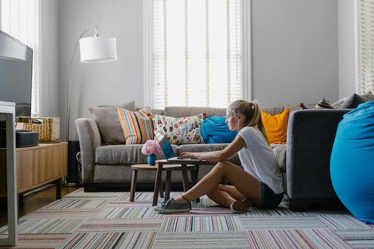 Teen Girl Seated in Living Room doing Homework