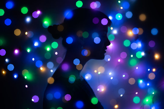 Silhouette of a woman surrounded by lights