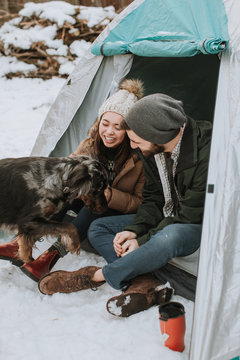 Couple Sitting in Tent at Campsite with Dog