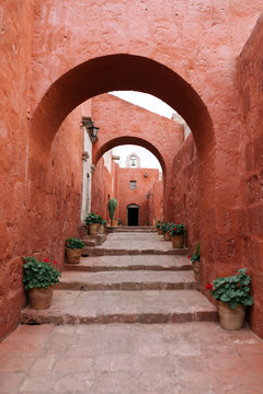 Red walls with arches on street in Peru
