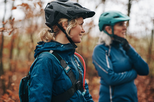 Smiling daughter and mother peparing to go mountain biking toget