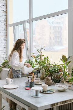 The attractive woman watering flowers in the apartment, Woman watering plant in container on balcony garden