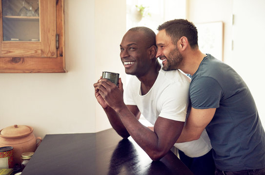 Gay couple embracing in kitchen and smiling together