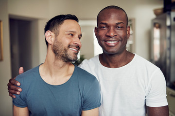 Happy adult gay couple embracing at home