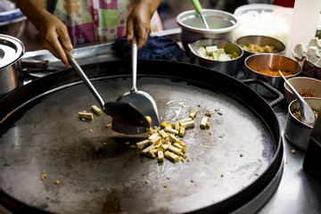 Woman preparing Vegetarian Pad Thai in a street food market