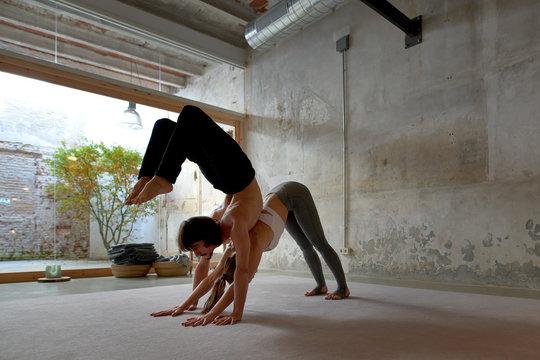 Sportive couple doing yoga in studio