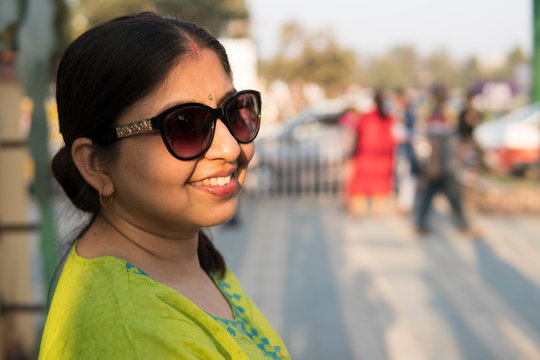 Woman wearing sunglasses and laughing in city