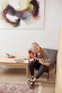 Inspired man playing guitar in armchair