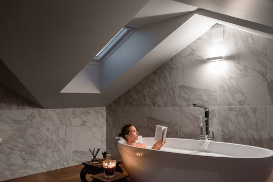 Content woman with book in hot bathtub