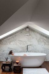 Woman in solitude lying in white bathtub at home