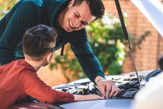 The father and son fixing under the car hood