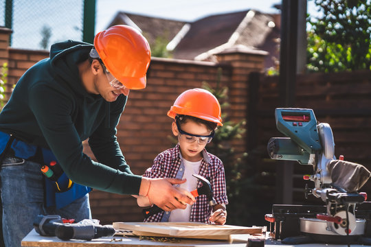 The father teaches his son how to use hammer and nails