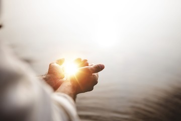 Beautiful shot of Jesus Christ holding hope and light in his palms with a blurred background
