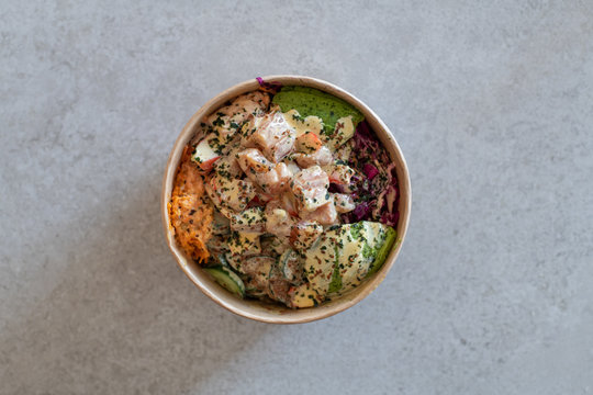California Poke Bowl with salmon, avocado,  crab surimi, carrot, red cabbage, ginger, sushi rice and cucumber