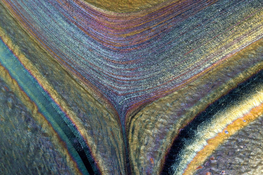 Closeup of patterns, colors and textures in a hand-made glass vase.