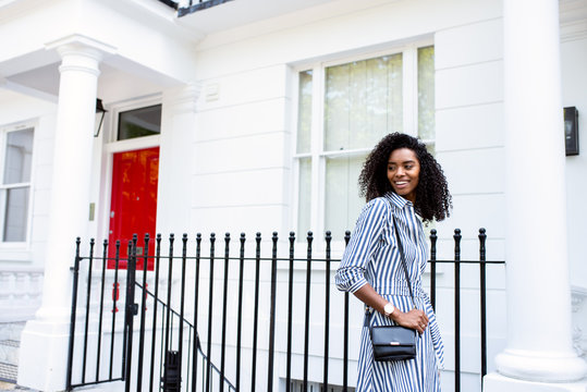 Woman walking by beautiful white houses facades