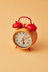 Old yellow alarm clock with red bells on an yellow background, copy space.