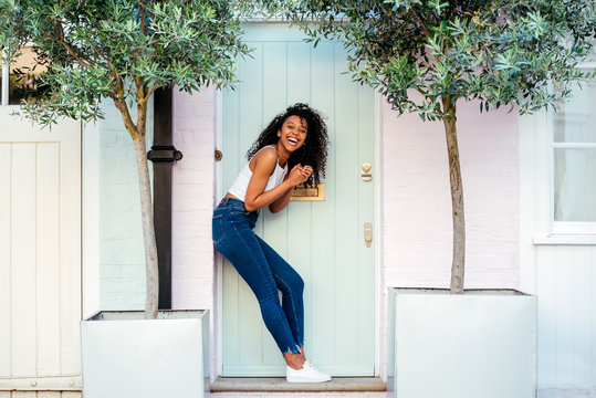 Woman leaning in a beautiful pink and blue door