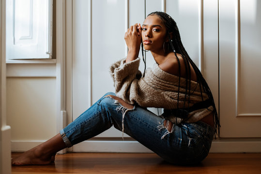 Beautiful black woman with braided long hair sitting in the floor