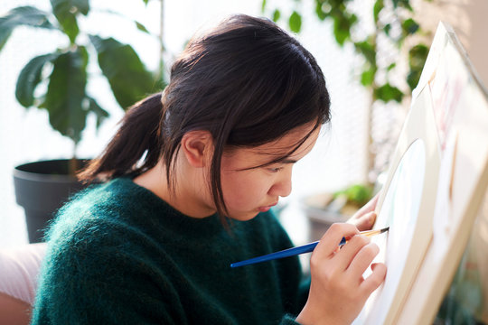 Asian teens are painting, balcony in the sun