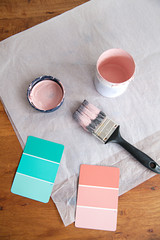Pink and green color swatches for paint on table top with paint brush and paint
