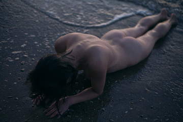 girl without clothes posing lying on the seashore