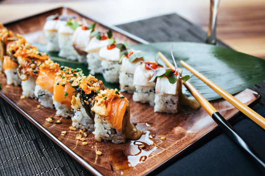 A plate of two sushi rolls with chopsticks