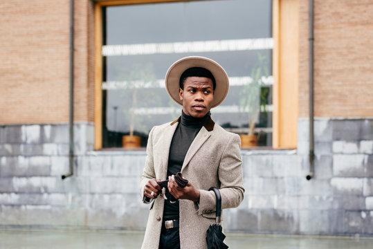 Elegant man with grey coat in the street