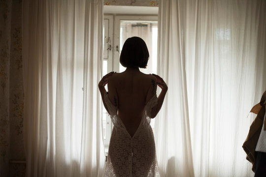 girl takes off her dress on the background of curtains at home