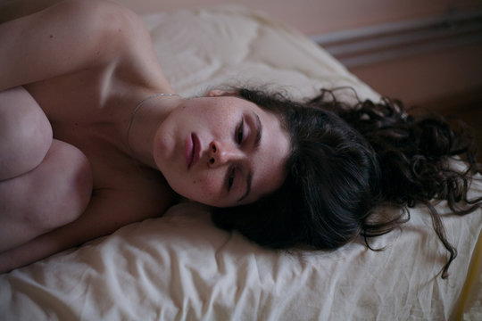 sad girl portrait with freckles without clothes on a bed with loose black hair
