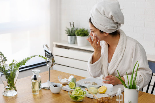 Young woman applying face mask at home. Natural Skin Care Routine. Cleaning face with natural cosmetics.