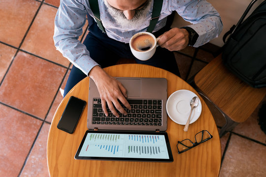 Unrecognizable senior businessman having coffee and working with his laptop
