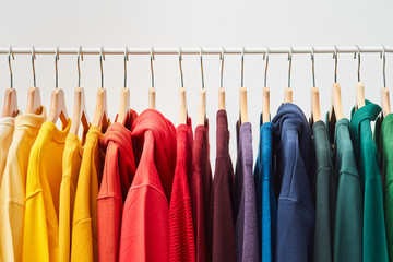 Rainbow colored clothes on rack