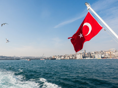 Flag of Turkey on boat between water near city