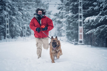 Man running with dog on way between winter forest