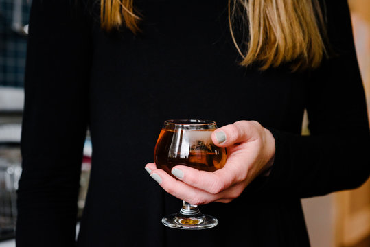 Woman Holding a Glass of Scotch on the Rocks