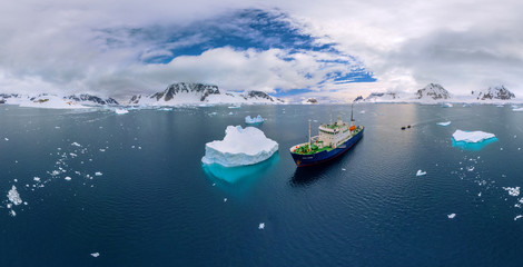 Aerial view Polar Pioneer, a scientific ship sailing near to an iceberg in Antarctica.