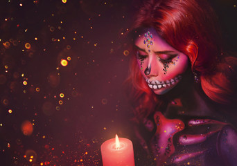 woman with creative multi-colored makeup sugar skull with stones and slices, holding a burning candle in her hands. greasepaint body art, aqua paints. Free space for text. Celebrate Dia de los Muertos
