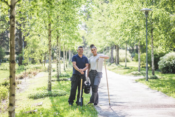 Full length portrait of smiling female trainee standing with male instructor holding gardening equipment on footpath at