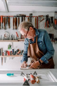 Senior male entrepreneur scraping window frame on workbench at store workshop