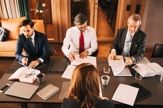High angle view of female financial advisor planning with male lawyers in meeting at board room