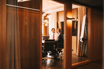 Male financial advisors discussing in board room at law office